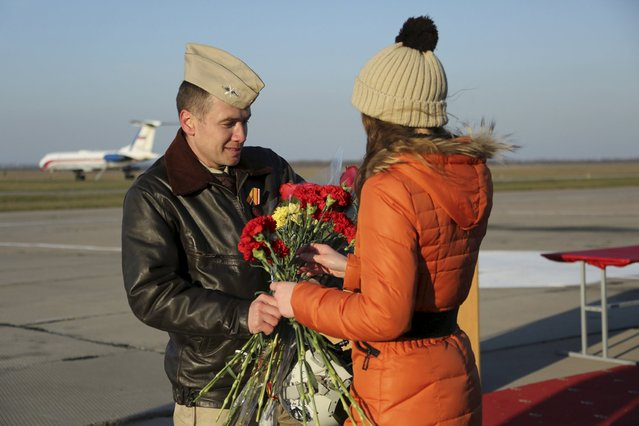 A pilot receives flowers during a ceremony to welcome Russian military aircraft and pilots arriving from Syria, at an airbase in Krasnodar region, southern Russia, in this March 16, 2016 handout photo by the Russian Ministry of Defence. (Photo by Olga Balashova/Reuters/Russian Ministry of Defence)