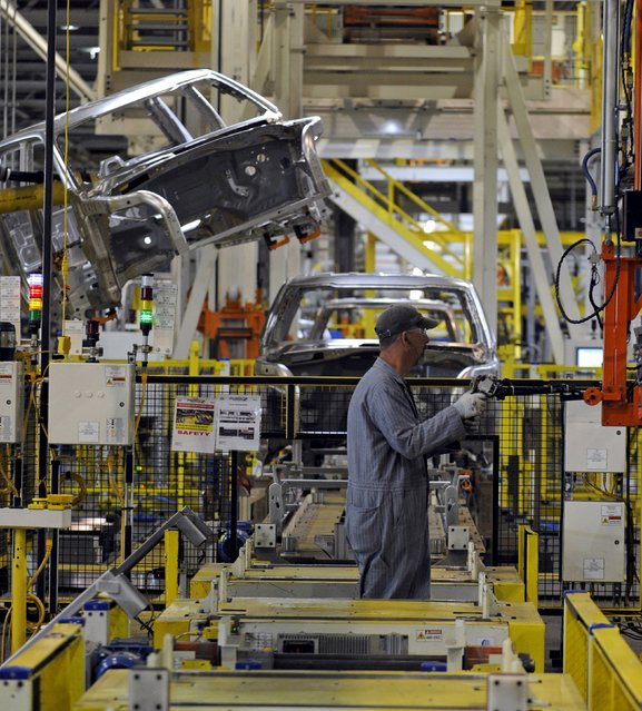 An auto worker assembles a skid as a truck cab is being lifted into position at Ford's Kansas City Assembly Plant where new aluminum intensive Ford F-Series pickups are built in Claycomo, Missouri May 5, 2015. (Photo by Dave Kaup/Reuters)