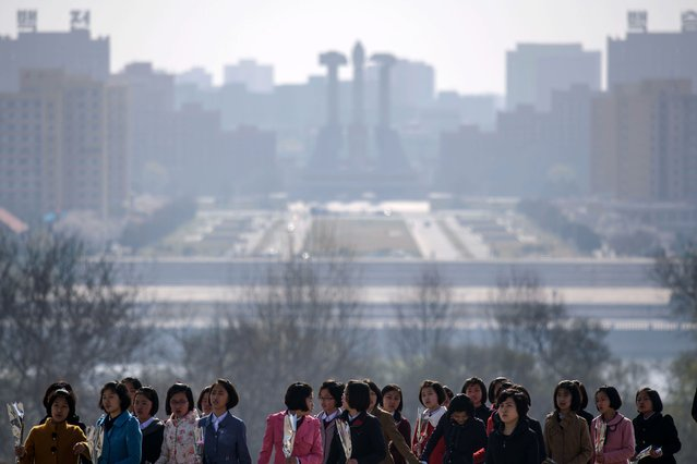 "People arrive to pay their respects before the statues of late North Korean leaders Kim Il Sung and Kim Jong Il, as part of celebrations marking the anniversary of the birth of Kim Il Sung, known as the ""Day of the Sun"", on Mansu hill in Pyongyang on April 15, 2019. (Photo by Ed Jones/AFP Photo)"