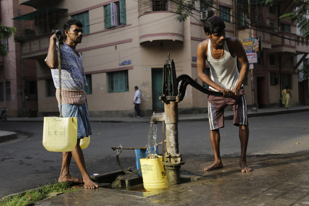"A water man or locally called as ""bhari"" fills drinking water from a roadside hand pump while another waits to deliver in houses in Kolkata, India, Tuesday, March 22, 2016. A report says India has the world's highest number of people without access to clean water. The international charity Water Aid says 75.8 million Indians or 5 percent of the country's 1.25 billion population are forced to either buy water at high rates or use supplies that are contaminated with sewage or chemicals. (Photo by Bikas Das/AP Photo)"