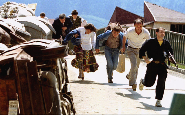 A group of Bosnian civilians, led by a policeman, run a gauntlet of wrecked cars acting as shields from Bosnian Serb snipers in the Sarajevo suburb of Dobrinja, June 1993. (Photo by Chris Helgren/Reuters)