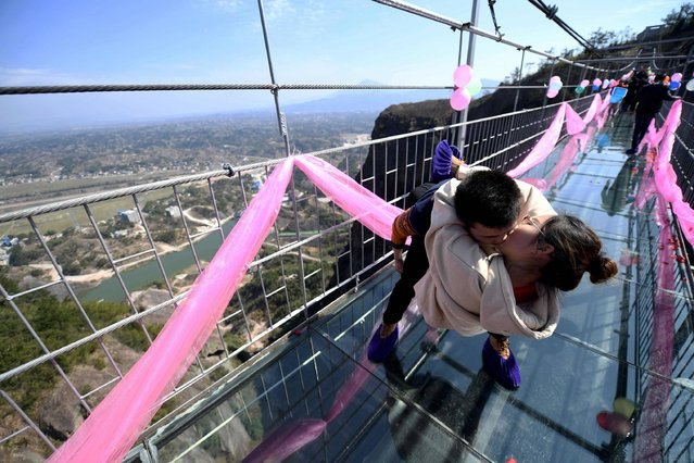 A Chinese couple kiss as they stand on a glass bridge during a kissing contest on Valentine's Day in Pingjiang, central China's Hunan province on February 14, 2017. (Photo by AFP Photo/Stringer)