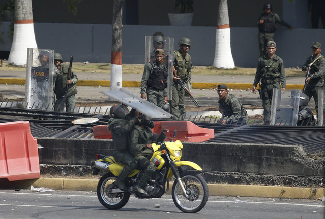 National Guards stand behind a fallen section of fencing on the perimeter of La Carlota airbase during clashes with anti-government protesters in Caracas, Venezuela, Wednesday, May 1, 2019. (Photo by Ariana Cubillos/AP Photo)