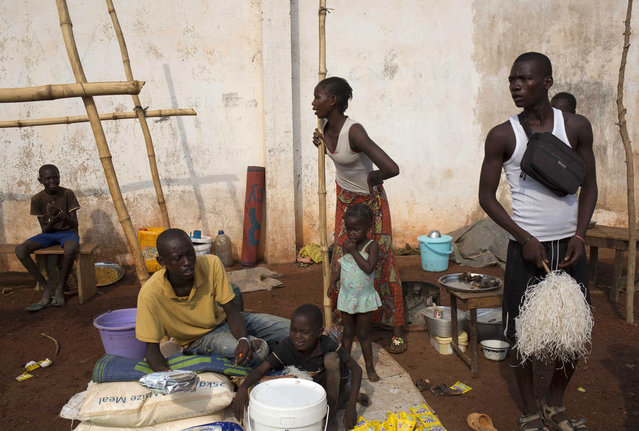 A family gathers at a camp for displaced people at M'poko International Airport in Bangui February 26, 2014. (Photo by Camille Lepage/Reuters)