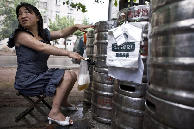 A vendor pours fresh Tsingtao beer into a plastic bag in her street beer shop in Qingdao, Shandong province July 5, 2008. (Photo by Nir Elias/Reuters)