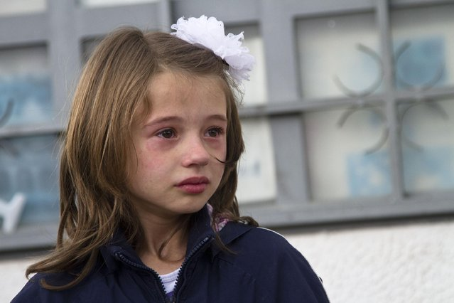 A girl weeps after she was evacuated safely from the scene of an altercation involving the police, in northern Macedonian town of Kumanovo, on Saturday, May 9, 2015. Authorities in Macedonia say police have clashed with an armed terrorist group in this northern Macedonian town, and parts of the town have been sealed off. Macedonia's state-run news agency MIA reported that four police officers were injured by gunfire, and three of them were taken to a hospital in the capital, Skopje. (Photo by Visar Kryeziu/AP Photo)