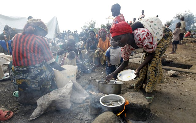 A Burundian refugee cooks a meal on the shores of Lake Tanganyika in Kagunga village in Kigoma region in western Tanzania, as they wait for MV Liemba to transport them to Kigoma township, May 18, 2015. (Photo by Thomas Mukoya/Reuters)