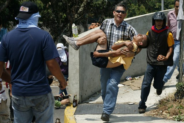 A man carries an injured anti-government protester during a protest against Venezuela's President Nicolas Maduro's government in San Cristobal March 18, 2014. A Venezuela National Guard captain died on Monday after being shot in the head during a demonstration, the military said, the 29th fatality in six weeks of clashes between protesters and security forces. (Photo by Carlos Eduardo/Reuters)