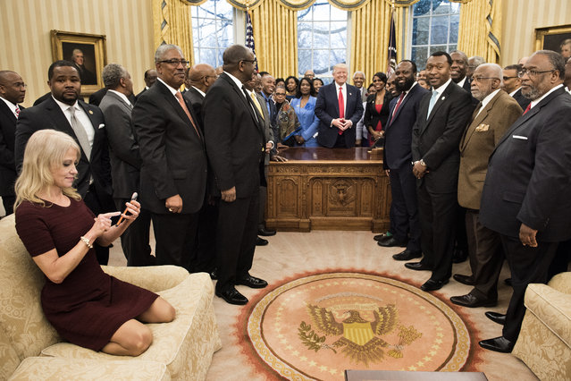 Counselor to the President Kellyanne Conway (L) checks her phone after taking a photo as US President Donald Trump and leaders of historically black universities and colleges pose for a group photo in the Oval Office of the White House before a meeting with US Vice President Mike Pence February 27, 2017 in Washington, DC. (Photo by Brendan Smialowski/AFP Photo)