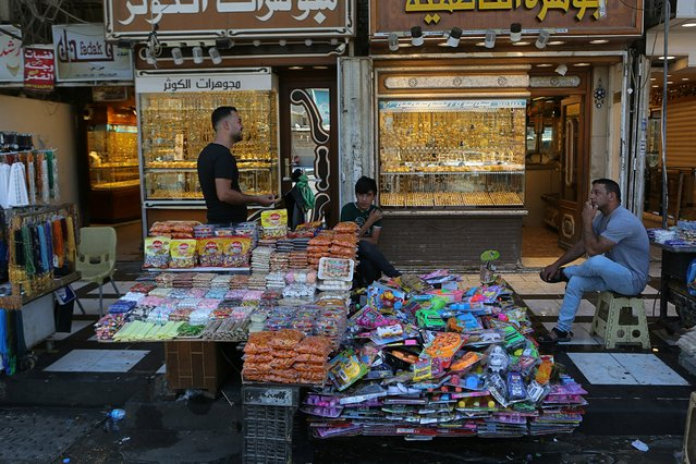 In this Wednesday, May 21, 2019, photo, street vendors and shop owners wait for customers outside the shrine of Imam Moussa al-Kadhim in Kadhimiya district in north Baghdad, Iraq. Many shop owners in the Shiite holy neighborhood of Kadhimiya, have seen their sales drop sharply over the past year since U.S. President Donald began reimposing sanctions on Iran, home to the largest number of Shiite Muslims around the world. (Photo by Khalid Mohammed/AP Photo)