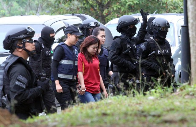 Suspect Siti Aisyah from Indonesia, center, in the ongoing assassination investigation, is escorted by police officers out from Sepang court in Sepang, Malaysia on Wednesday, March 1, 2017. Two women accused of smearing VX nerve agent on Kim Jong Nam, the estranged half brother of North Korea's leader, were charged with murder Wednesday after arriving in court under heavy protection. (Photo by AP Photo)