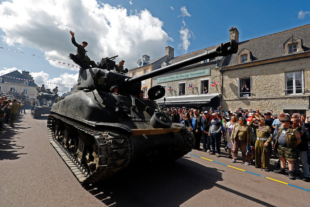 WWII enthusiasts on tanks participate in a parade to commemorate the 75th anniversary of the Allied landings on D-Day, in Sainte-Mere-Eglise, Normandy, France, 06 June 2019. World leaders are attending memorial events in Normandy on the day to mark the 75th anniversary of the D-Day landings, which marked the beginning of the end of World War II in Europe. (Photo by Sébastien Nogier/EPA/EFE)