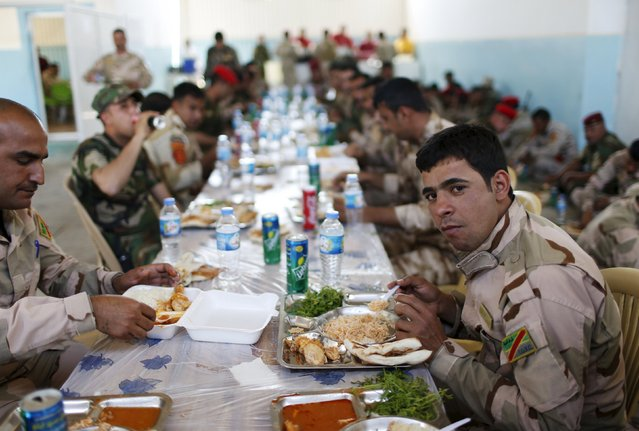 Iraqi soldiers have their lunch at their base in Makhmour, after it was freed from control of Islamic State, south of Mosul, April 17, 2016. (Photo by Ahmed Jadallah/Reuters)