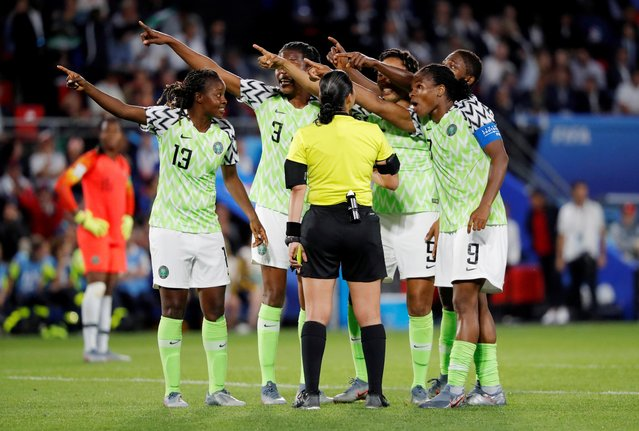 Nigerian players points towards the electronic screen as they protest a yellow card and a penalty awarded against their goalkeeper Chiamaka Nnadozie by referee Melissa Borjas of Honduras, center, during the Women's World Cup Group A soccer match between Nigeria and France at the Roazhon Park in Rennes, France, Monday, June 17, 2019. (Photo by Stephane Mahe/Reuters)