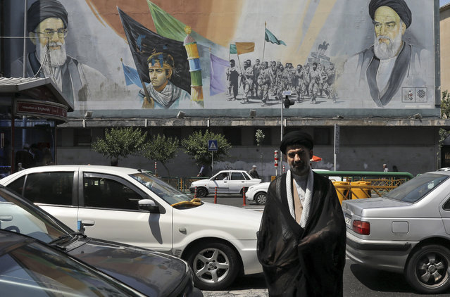 In this Friday, May 17, 2019 photo, a cleric crosses Enqelab-e-Eslami (Islamic Revolution) street in front of a mural depicting late Iranian revolutionary founder Ayatollah Khomeini, right, Supreme Leader Ayatollah Ali Khamenei, left, and the Basij paramilitary force, in downtown Tehran, Iran. (Photo by Vahid Salemi/AP Photo)