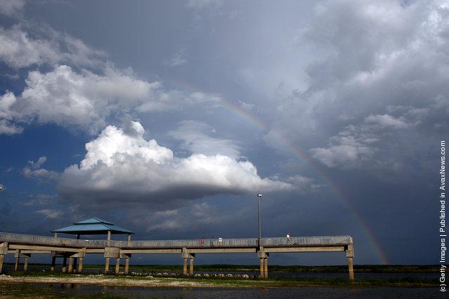 A rainbow graces the sky over a pier built over what should be lake Okeechobee in Okeechobee, Florida
