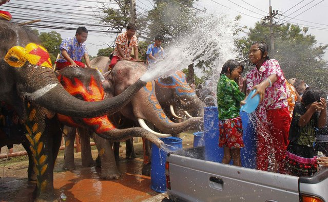 Elephants spray water at children in celebration of the Songkran water festival in Thailand's Ayutthaya province, April 9, 2014. (Photo by Chaiwat Subprasom/Reuters)