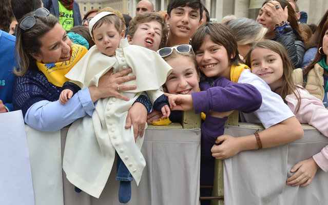 A mother holds her baby dressed as a pope as they wait Pope Francis upon his arrival on St. Peter's square at the Vatican to lead his weekly general audience on April 9, 2014. (Photo by Alberto Pizzoli/AFP Photo)