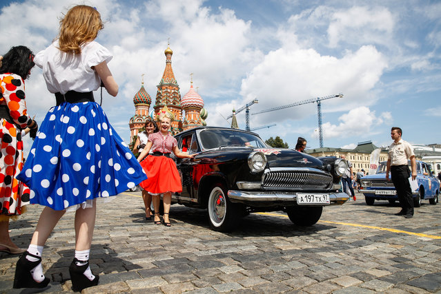 Women take pictures by a vintage car during the 2019 GUM Motor Rally featuring classic cars in Moscow, Russia on July 28, 2019. The youngest car at this year's rally is 35, the oldest – a GAZ-A convertible – is 85. (Photo by Artyom Geodakyan/TASS via Getty Images)