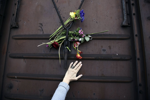 A woman places flowers on a train wagon at the old train station in Thessaloniki, Greece on Sunday, March 19, 2017. Residents of this northern Greek city on Sunday visited the train station to mark the 74th anniversary of the roundup and deportation of its Jews to Nazi extermination camps during World War II. (Photo by Giannis Papanikos/AP Photo)