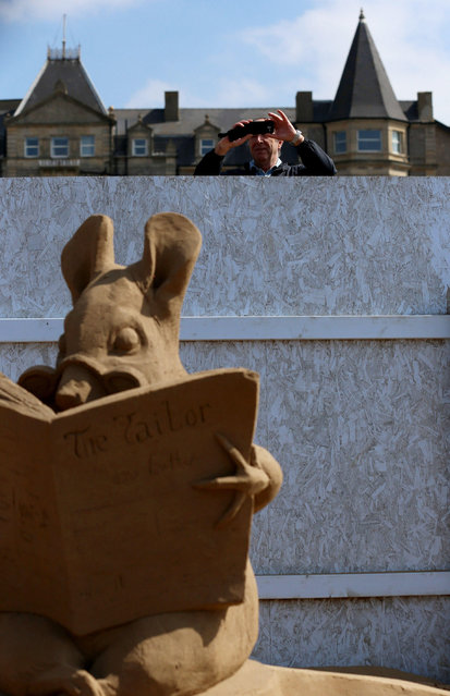 "People try to peek a look of the sand sculpture exhibition as final preperations are made to this year's ""Once Upon a Time"" themed annual Weston-super-Mare Sand Sculpture festival on April 16, 2014 in Weston-Super-Mare, England. (Photo by Matt Cardy/Getty Images)"