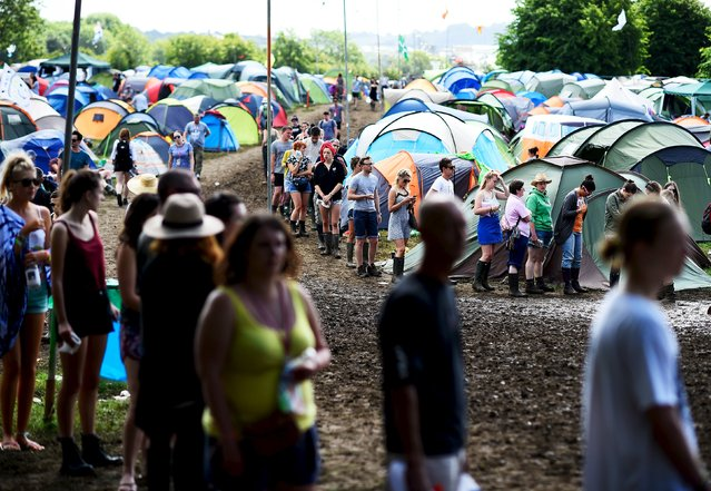 Revellers queue for the lavatories at Worthy Farm in Somerset during the Glastonbury Festival in Britain, June 27, 2015. (Photo by Dylan Martinez/Reuters)