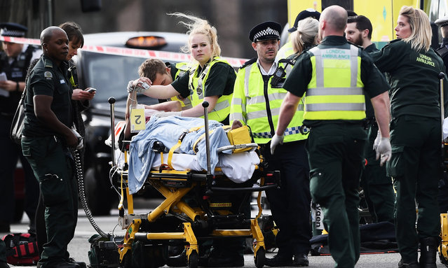 A member of the public is treated by emergency services near Westminster Bridge and the Houses of Parliament on March 22, 2017 in London, England. A police officer has been stabbed near to the British Parliament and the alleged assailant shot by armed police. Scotland Yard report they have been called to an incident on Westminster Bridge where several people have been injured by a car. (Photo by Carl Court/Getty Images)