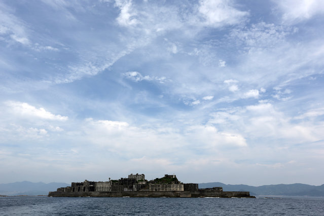"In this June 29, 2015 photo, Hashima Island, commonly known as Gunkanjima, which means ""Battleship Island"", is seen off Nagasaki, Nagasaki Prefecture, southern Japan. (Photo by Eugene Hoshiko/AP Photo)"