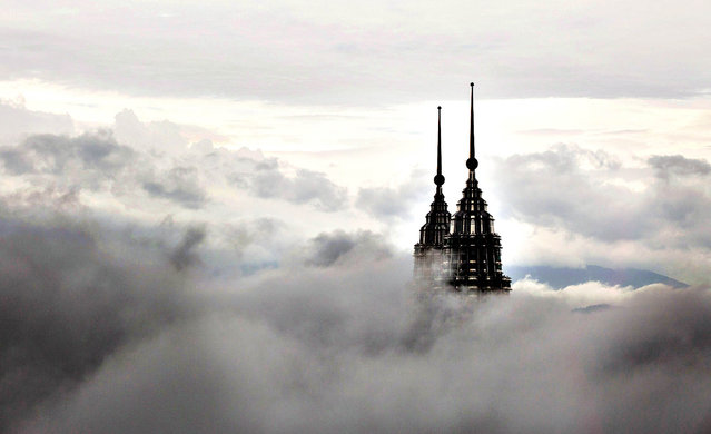 The pinnacles of the Petronas Twin Towers protrude through low clouds in Kuala Lumpur, Malaysia, on Tuesday, March 18, 2014. (Photo by Charles Pertwee/Bloomberg)