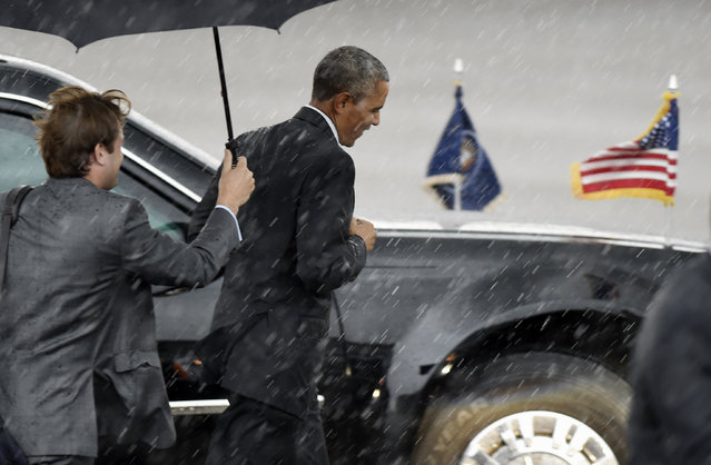 President Barack Obama jogs back to his limo in the heavy rain after he arrived, Wednesday, July 1, 2015, in Nashville, Tenn. The president is scheduled to speak at an elementary school regarding the Affordable Care Act. (Photo by Sanford Myers/AP Photo)