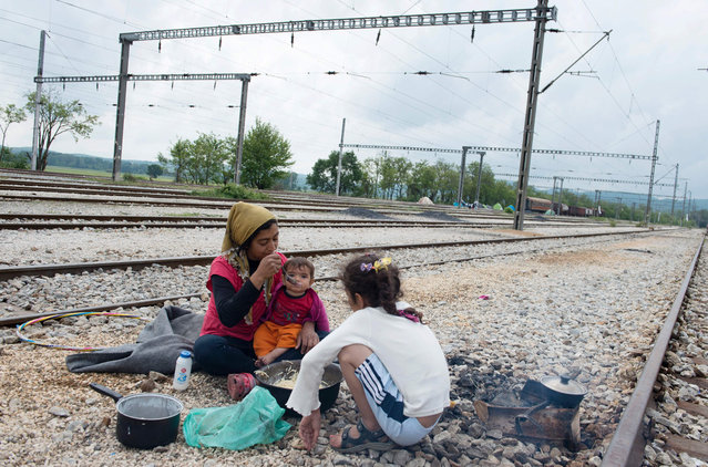 A woman feeds a child next to rail tracks at a migrants and refugees makeshift camp at the Greek-Macedonian border near the village of Idomeni on May 2, 2016. Some 54,000 people, many of them fleeing the war in Syria, have been stranded on Greek territory since the closure of the migrant route through the Balkans in February. (Photo by Tobias Schwarz/AFP Photo)