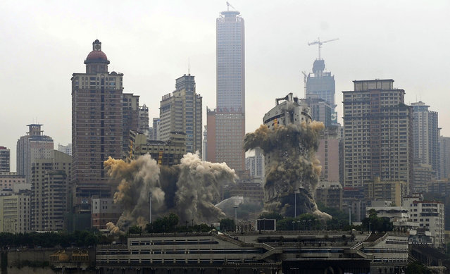 A view shows the Three Gorges Hotel (L) and the passenger terminal of Chongqing Port (R) collapsing after demolition by explosives in Chongqing, southwest China, August 31, 2012. (Photo by Reuters/China Daily)