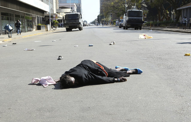A woman lies in the road after been injured by police during protests in Harare, Friday, August 16, 2019. The main opposition Movement For Democratic Change party is holding protests over deteriorating economic conditions in the country as well as to try and force Zimbabwean President Emmerson Mnangagwa to set up a transitional authority to address the crisis and organize credible elections. (Photo by Tsvangirayi Mukwazhi/AP Photo)