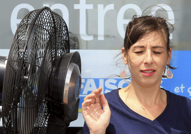 A store employee cools off by an electric fan  in Anglet, southwestern France, Friday, July 3, 2015, wherethe temperature rose to 32 degrees (89,6 Farenheit). A mass of hot air moving north from Africa is bringing unusually hot weather to Western Europe. (Photo by Bob Edme/AP Photo)