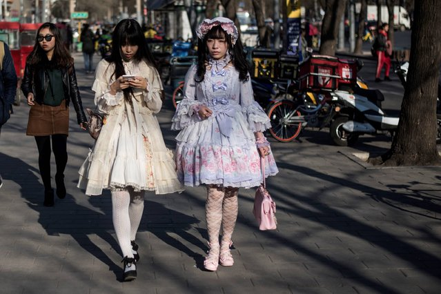 Two girls in cosplay dresses walk in the street in Beijing on March 27, 2017. (Photo by Fred Dufour/AFP Photo)