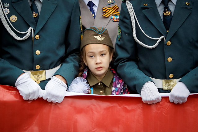 A girl wearing dress styled as Soviet army's uniform stands between cadets during a march at Victory Day commemorations in  Almaty, Kazakhstan, May 9, 2016. (Photo by Shamil Zhumatov/Reuters)