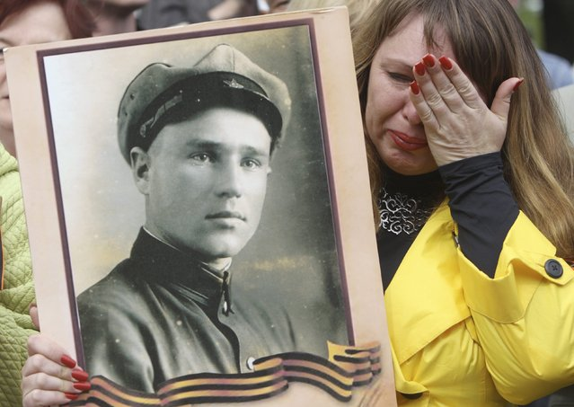 A woman holds a portrait of a former Soviet serviceman during events to mark Victory Day in the Eastern Ukrainian city of Lugansk May 9, 2014. (Photo by Valentyn Ogirenko/Reuters)