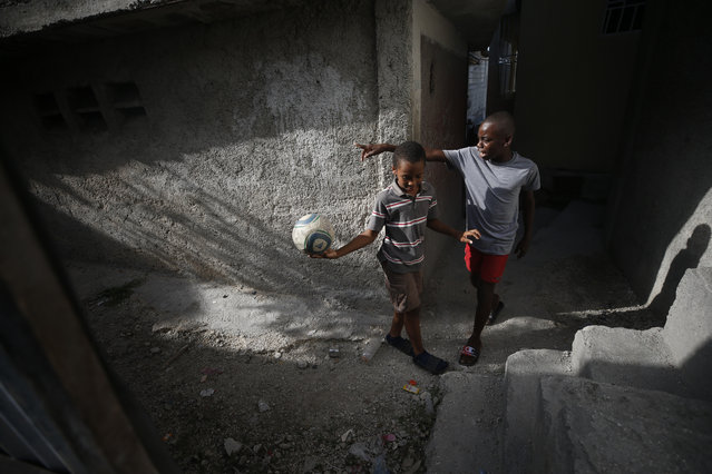 Children play with a soccer ball in an alley between homes inside the Delmas neighborhood of Port-au-Prince, Haiti, Tuesday, October 8, 2019. With schools still shuttered and parents worried about a climate of insecurity with protests calling for the resignation of the president now in their fourth week, few children are visible on the capital's streets. (Photo by Rebecca Blackwell/AP Photo)