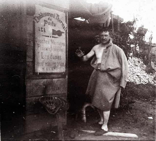 "An undated archive picture shows a French soldier after taking a shower, at the rear guard near the front line, at an unknown location in France. The placard reads ""Thermal complex of the Poilu, showers, massages, chiropodist, manicurist. Free massages for women"". (Photo by Collection Odette Carrez/Reuters)"