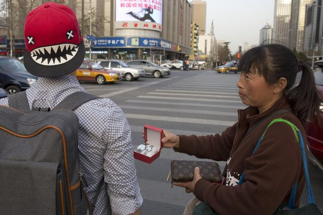 In this photo taken Friday, March 20, 2015, a street vendor hawks counterfeit branded items to tourists on the streets of Beijing. (Photo by Ng Han Guan/AP Photo)