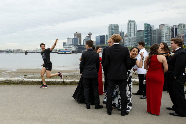Prime Minister Justin Trudeau jogs past a group of high school students dressed for their prom in Vancouver, British Columbia, Canada on May 19, 2017. (Photo by Adam Scotti/Reuters/Courtesy Prime Minister's Office)