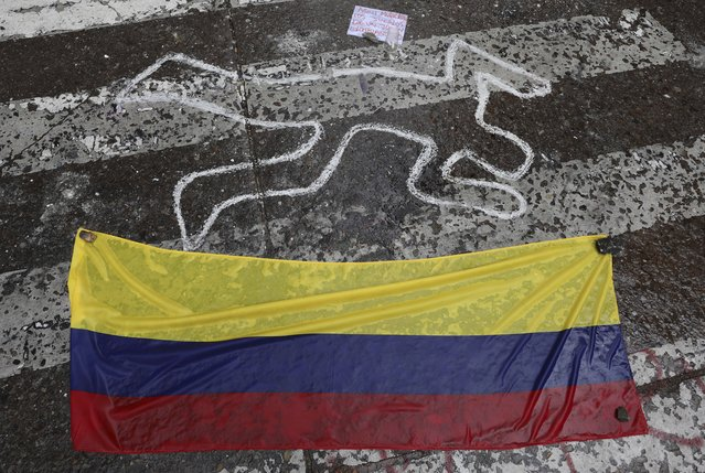 A Colombian national flag lays at the site where Dilan Cruz was injured during clashes between anti-government protesters and security forces, in Bogota, Colombia, Tuesday, November 26, 2019. Cruz, an 18-year-old high school student, died two days after being hit in the head by a projectile reportedly fired by riot police during a protest. His case has resonated in Colombian society, touching off a debate about excessive use of force and making him a symbol for many young protesters. (Photo by Fernando Vergara/AP Photo)