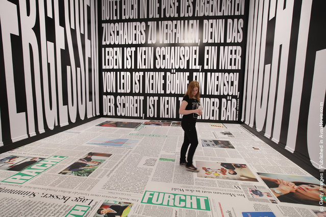 A young woman walks through an installation by artist Barbara Kruger at the exhibition ARTandPRESS at Martin Gropius Bau