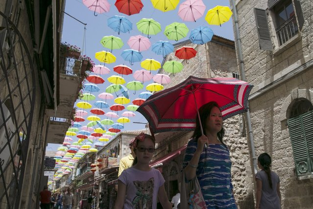 A woman holds an umbrella as she walks under an installation of some 1,000 colourful umbrellas decorating a pedestrian mall in Jerusalem July 27, 2015. (Photo by Baz Ratner/Reuters)