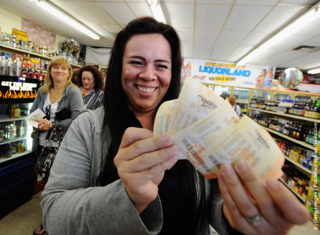 Victoria Vazquez displays $280 worth of Mega Millions lottery tickets for her office pool that she purchased at Liquorland