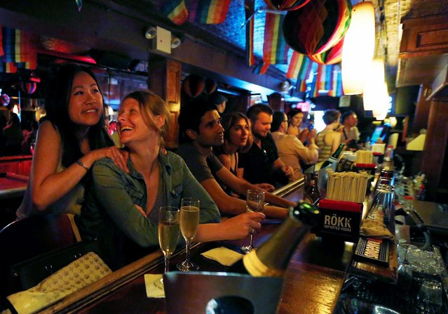 Patrons celebrate as they watch coverage of the U.S. Supreme Court ruling on the Defense of Marriage Act at the Stonewall Inn in New York June 26, 2013. (Photo by Brendan McDermid/Reuters)