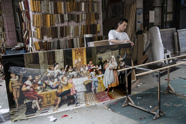 A framer works on a reproduction canvas at the artist village on June 12, 2014 in Shenzhen, China. The Dafen Artist Village in Guangdong province, China, is home to thousands of artists who reproduce some of the world's most iconic paintings as well as create their own works. The village, on the outskirts of Shenzhen, is becoming a major center for original Chinese art. (Photo by Palani Mohan/Getty images)