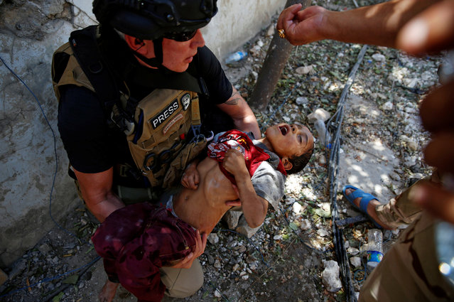 Iraqi soldiers from 9th Armoured Division give drops of water to a dehydrated child rescued earlier by soldiers at the frontline, during the ongoing fighting between Iraqi forces and Islamic State militants near the Old City in western Mosul, Iraq June 13, 2017. (Photo by Erik De Castro/Reuters)
