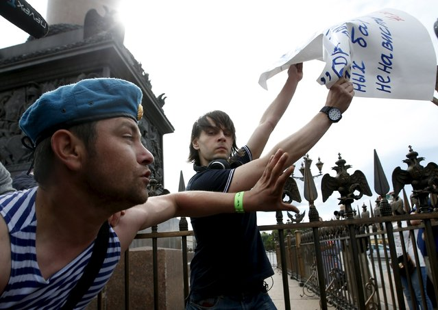 "A man (L) celebrating Paratroopers Day attempts to take away a placard of a gay rights activist who is taking part in a protest in Dvortsovaya Square in St. Petersburg, Russia, August 2, 2015. The holiday for the Russian airborne troops has been annually celebrated since the Soviet era till today. The placard bears a quote of Charlie Chaplin in the film The Great Dictator: ""Let us fight to free the world, to do away with national barriers, to do away with greed, with hate and intolerance"". (Photo by Maxim Zmeyev/Reuters)"