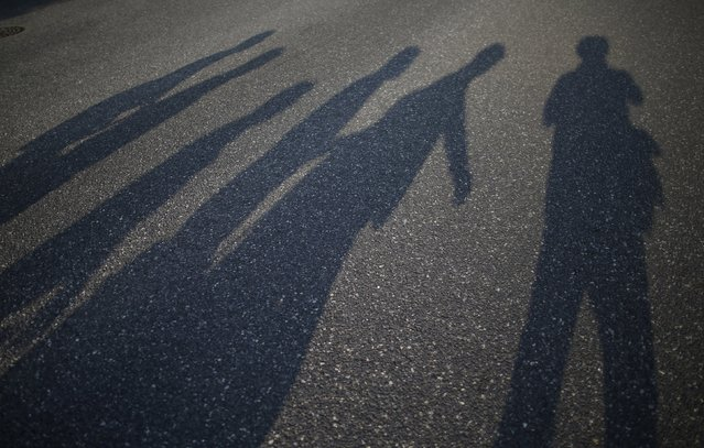 Reuters photographer Issei Kato (R) and passersby cast shadows on a street in Hiroshima, western Japan July 28, 2015. (Photo by Issei Kato/Reuters)